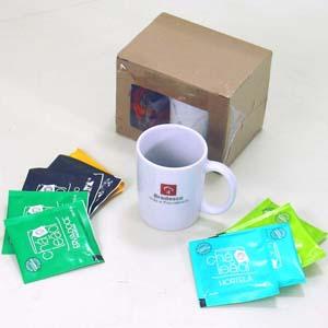 Brindes da Terra - Mini kit de chá na caixa de papelão kraft micro ondulado vincado com visor frontal. Inclusos: Caneca de porcelana branca com modelo cappuccino gravada...