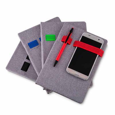 brindes-de-luxo - Caderno porta caneta e celular tecido sintético. Elástico colorido e caderno cinza, possui aproximadamente 80 páginas pardas pautadas. Tamanho:  21,4...