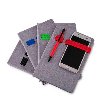 Abra Promocional - Caderno porta caneta e celular tecido sintético. Elástico colorido e caderno ciza, possui aproximadamente 80 páginas pardas pautadas.