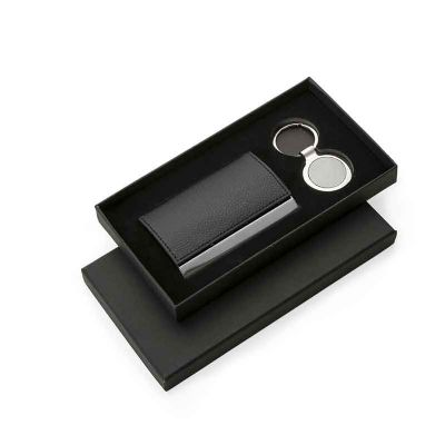 J.E Brindes - Kit porta cartão e chaveiro metal. Embalagem de papelão com parte interna de veludo, porta cartão em couro sintético com detalhe em metal e parte inte...