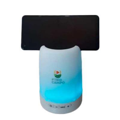 Genialle Brindes & Personalizados - Caixa de som multimídia com luzes, suporte para celular e porta caneta. Material plástico resistente na cor branca fosca, parte superior com auto fala...